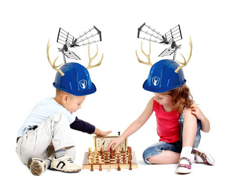2 young kids playing chess with genius hat